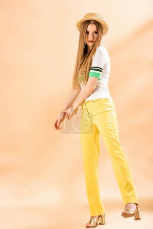 Photo for Stylish young woman posing in yellow trousers, polo and straw hat on beige - Royalty Free Image