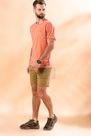 """Photo pour Bel homme élégant posant en shorts et t-shirt d """"été sur beige - image libre de droit"""