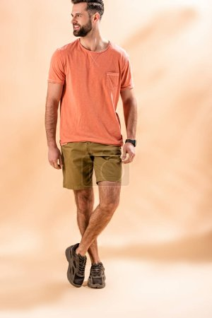cheerful stylish man posing in shorts and summer t-shirt on beige