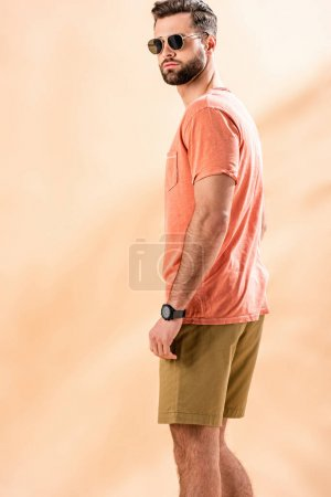 Photo for Handsome young man posing in shorts, summer t-shirt and sunglasses on beige - Royalty Free Image