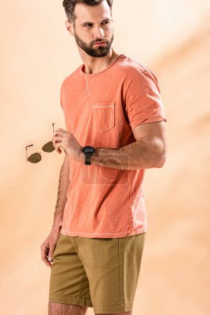 Photo for Handsome stylish man posing in shorts and summer t-shirt holding sunglasses on beige - Royalty Free Image