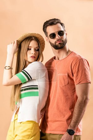 Photo for Fashionable beautiful couple posing in summer clothes, straw hat and sunglasses on beige - Royalty Free Image