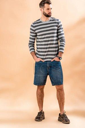 Photo for Stylish bearded man posing in striped sweatshirt on beige - Royalty Free Image