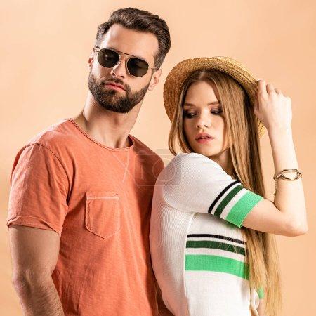 Photo pour Beau couple à la mode posant en vêtements d'été, chapeau de paille et lunettes de soleil sur beige - image libre de droit