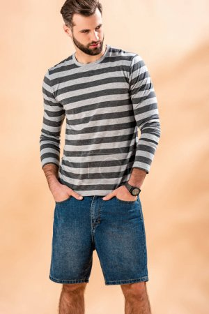 Photo for Handsome bearded man posing in striped sweatshirt on beige - Royalty Free Image