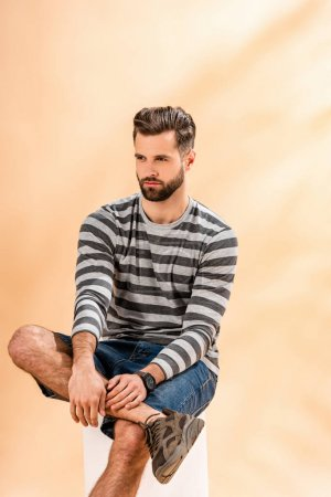 Photo pour Homme barbu à la mode en sweat-shirt rayé assis sur cube blanc sur beige - image libre de droit