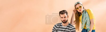panoramic shot of beautiful stylish couple posing in summer clothes on beige