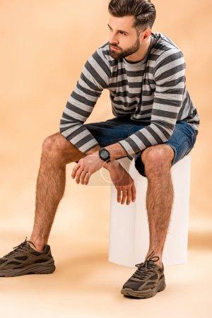 handsome stylish bearded man in striped sweatshirt sitting on white cube on beige