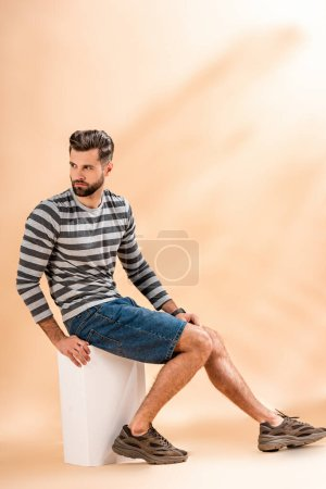 Photo for Handsome bearded man in striped sweatshirt sitting on white cube on beige - Royalty Free Image