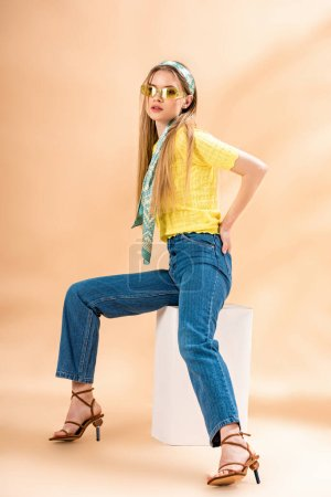 Photo for Beautiful stylish girl in jeans, yellow t-shirt, sunglasses, heeled sandals and silk scarf sitting on white cube on beige - Royalty Free Image