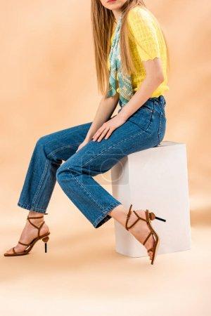 Photo pour Crochetée vue d'une fille en jeans, t-shirt jaune, sandales talonnées et foulard de soie sur beige - image libre de droit