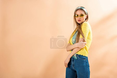 beautiful girl posing in jeans, yellow t-shirt, sunglasses and silk scarf on beige