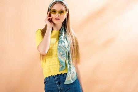 Photo pour Belle fille posant en jeans, t-shirt jaune, lunettes de soleil et foulard en soie sur beige - image libre de droit