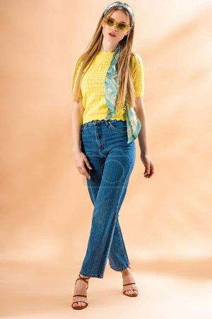 Photo pour Belle fille élégante posant en jeans, sandales à talons, lunettes de soleil et foulard en soie sur beige - image libre de droit