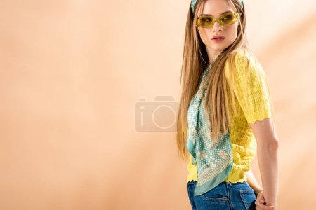 Photo for Beautiful stylish girl posing in jeans, yellow t-shirt, sunglasses and silk scarf on beige - Royalty Free Image