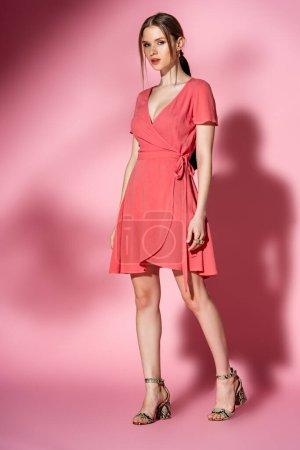 Photo pour Femme à la mode posant en robe d'été et sandales à talons sur rose - image libre de droit