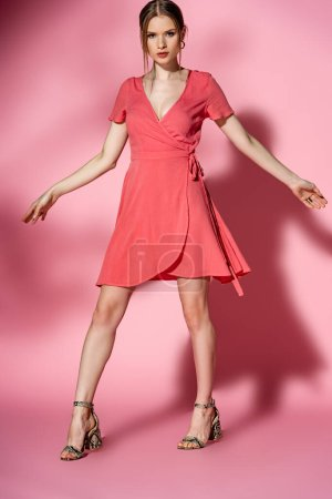 Photo pour Belle fille élégante posant en robe d'été et sandales à talons sur rose - image libre de droit