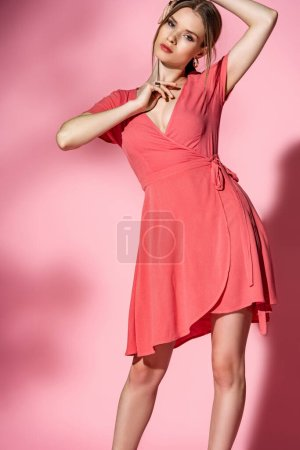 attractive fashionable young woman posing in summer dress on pink