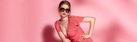 Photo pour Plan panoramique de jolie fille à la mode posant en robe d'été et lunettes de soleil sur rose - image libre de droit