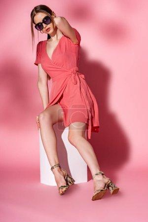 Photo pour Élégant jeune femme en robe d'été et lunettes de soleil assis sur cube blanc sur rose - image libre de droit