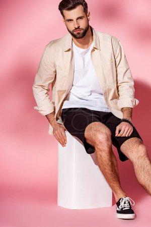Photo pour Homme barbu à la mode posant en chemise d'été et short sur cube blanc sur rose - image libre de droit