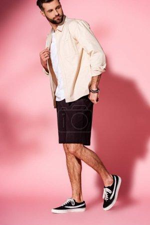 schöner bärtiger Mann posiert in Sommerhemd und Shorts auf rosa