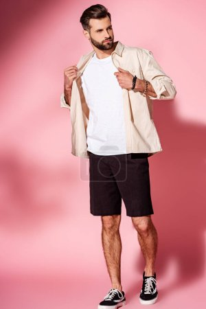 fashionable bearded man posing in summer shirt and shorts on pink