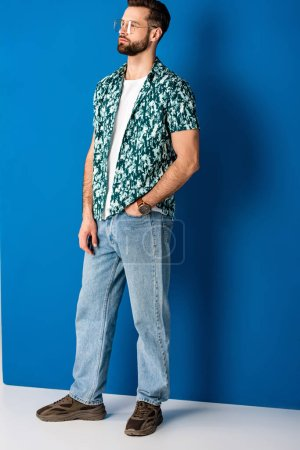Photo for Fashionable bearded man posing in summer clothes and sunglasses on grey and blue - Royalty Free Image
