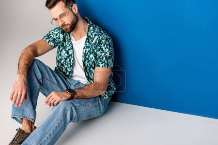 handsome bearded man posing in summer clothes and sunglasses on grey and blue