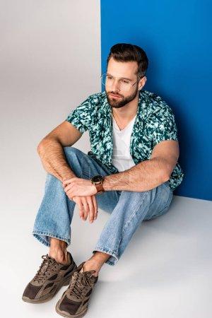 Photo pour Jeune homme à la mode posant en vêtements d'été et lunettes de soleil sur gris et bleu - image libre de droit