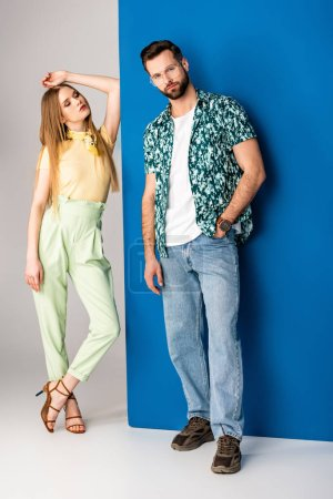 Photo for Fashionable young couple posing in summer clothes on grey and blue - Royalty Free Image