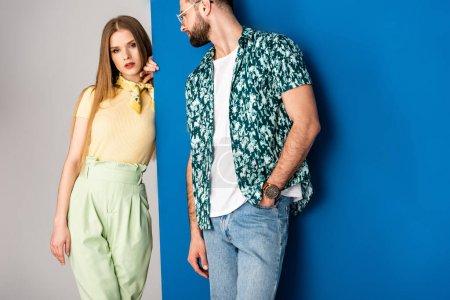 Photo pour Élégant jeune couple posant en vêtements d'été sur gris et bleu - image libre de droit