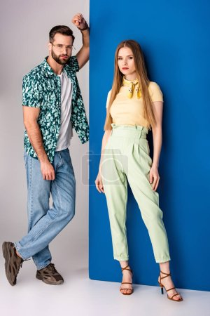 Photo for Stylish young couple posing in summer clothes on grey and blue - Royalty Free Image