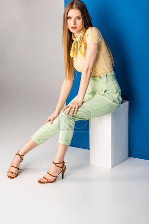Photo for Beautiful woman in green summer trousers and heeled sandals sitting on white cube on grey and blue - Royalty Free Image