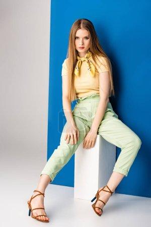 Photo pour Fille à la mode en vert pantalon d'été et sandales à talons assis sur cube blanc sur gris et bleu - image libre de droit