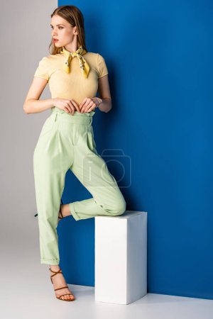 Photo for Attractive stylish woman posing in green summer trousers and heeled sandals on grey and blue - Royalty Free Image
