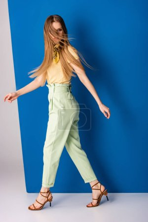 Photo for Beautiful fashionable girl posing in green summer trousers and heeled sandals on grey and blue - Royalty Free Image