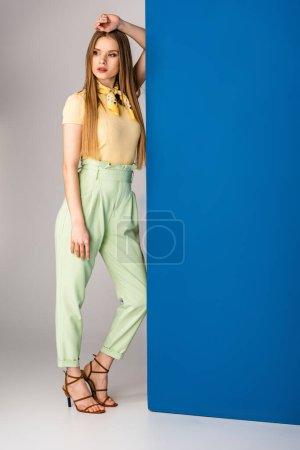 Photo pour Fille à la mode posant en pantalon vert d'été, t-shirt jaune et sandales à talons sur gris et bleu - image libre de droit
