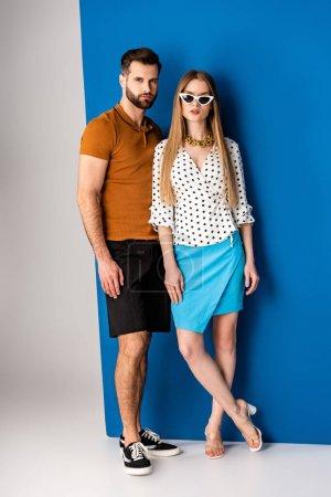 Photo pour Couple à la mode posant en vêtements d'été et lunettes de soleil sur gris et bleu - image libre de droit