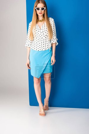 Photo for Stylish girl posing in polka dot blouse, blue skirt, heeled sandals and sunglasses on grey and blue - Royalty Free Image
