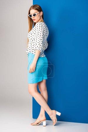 Photo pour Belle fille posant en chemisier à pois, jupe bleue, sandales à talons et lunettes de soleil sur gris et bleu - image libre de droit