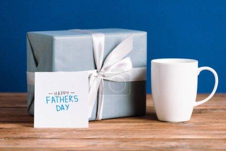 Photo pour Foyer sélectif de carte de vœux avec lettrage heureux jour des pères, tasse blanche et boîte cadeau avec arc blanc isolé sur bleu - image libre de droit