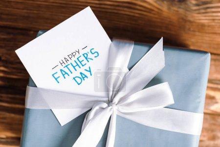 Foto de Vista superior de la tarjeta de felicitación con carta de padres felices día y caja de regalo con arco blanco sobre fondo de madera. - Imagen libre de derechos