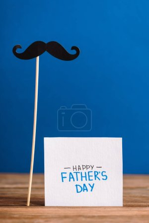 Photo for Selective focus of fake mustache from cardboard and greeting card with lettering happy fathers day isolated on blue - Royalty Free Image