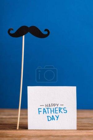 Photo pour Foyer sélectif de fausse moustache de carton et carte de vœux avec lettrage heureux jour des pères isolé sur bleu - image libre de droit