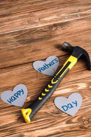 Photo pour Vue grand angle du marteau et du papier coeurs gris avec des mots heureux jour des pères sur fond en bois - image libre de droit
