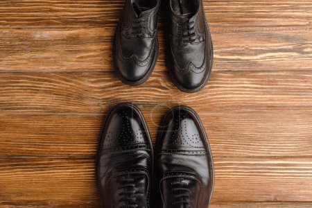 Photo for Top view of mens and childrens black elegant shoes on wooden background, fathers day concept - Royalty Free Image