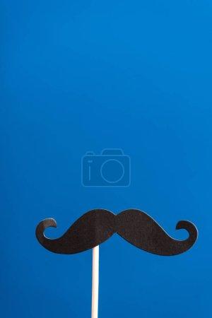Photo pour Papier noir décoratif fabriqué fausse moustache sur bâton blanc isolé sur bleu - image libre de droit