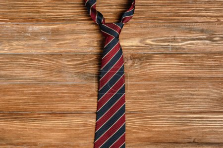 Photo for Top view of mens striped fabric tie on wooden background - Royalty Free Image