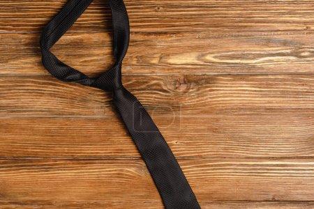Photo pour Vue de dessus de cravate noire unie mens sur fond en bois - image libre de droit